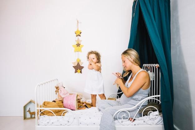 Femme tressant les cheveux près de bébé mignon