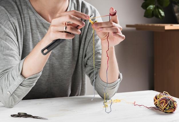 Femme tricotant avec une aiguille à la maison
