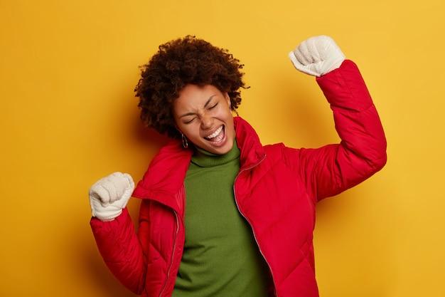 Femme triomphante ravie lève les bras, danse les yeux fermés