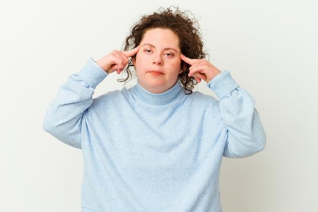 Femme trisomique isolée concentrée sur une tâche, gardant l'index pointant la tête.