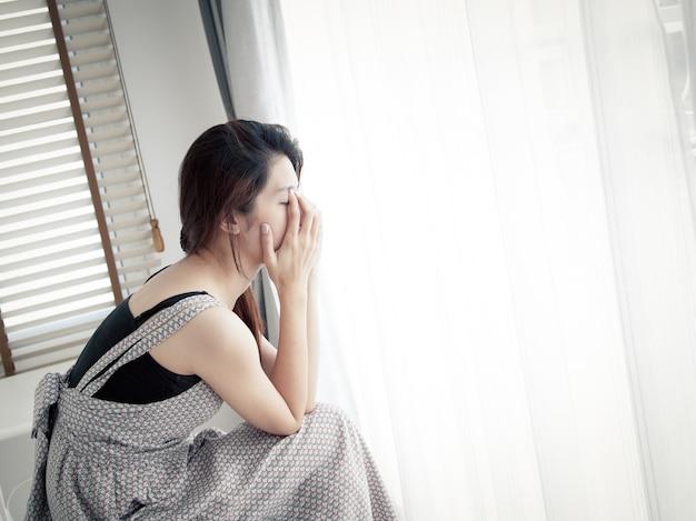 Femme triste assis seul dans la chambre