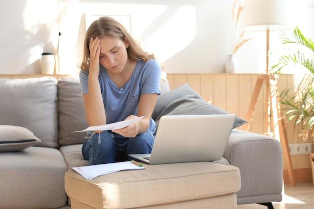 Femme triste assise sur un canapé dans le salon.