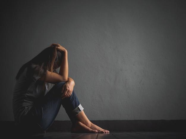 Femme triste assise seule, embrasse son genou et pleure.