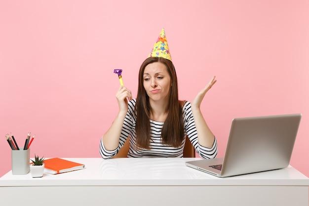 Femme triste au chapeau d'anniversaire avec un tuyau de jeu se sentant malheureux parce que personne n'est venu célébrer le travail assis au bureau blanc avec un ordinateur portable isolé sur fond rose. carrière commerciale de réussite. espace de copie.