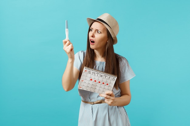 Femme triste choquée en robe bleue, chapeau à la main, test de grossesse, calendrier des périodes pour vérifier les jours de menstruation isolés sur fond bleu. concept médical, sanitaire, gynécologique. espace de copie.