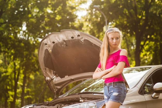 Femme triste et en colère avec voiture cassée