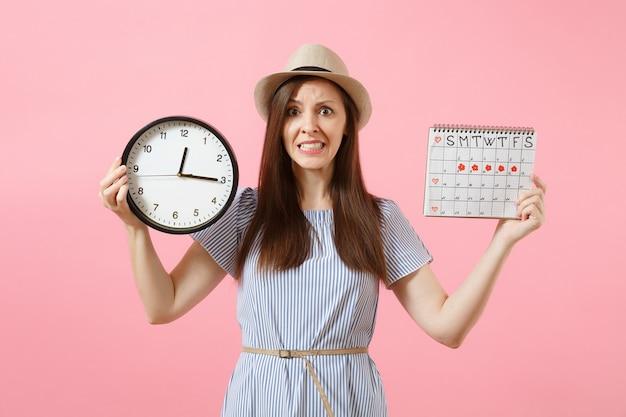 Femme triste confuse choquée en robe bleue tenant une horloge ronde, calendrier des périodes pour vérifier les jours de menstruation isolés sur fond rose tendance. concept gynécologique de soins médicaux. espace de copie