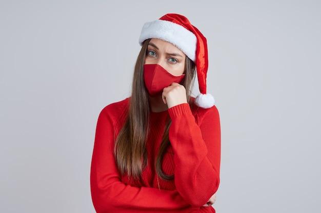 Femme triste dans un masque de protection, dans un bonnet de noel