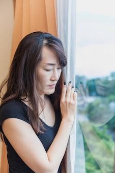 Femme triste et déprimée, debout à la fenêtre