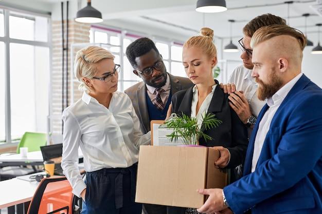 Une femme triste est mécontente de quitter son lieu de travail avec des collègues sympathiques