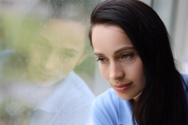 Une femme triste et fatiguée regarde par la fenêtre alors qu'il pleut un concept de dépression d'automne