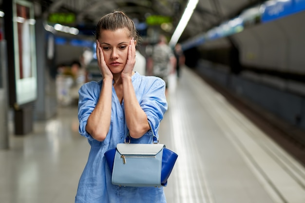 Femme triste à l'intérieur du métro en attente sur le quai d'une gare pour le train d'arriver.