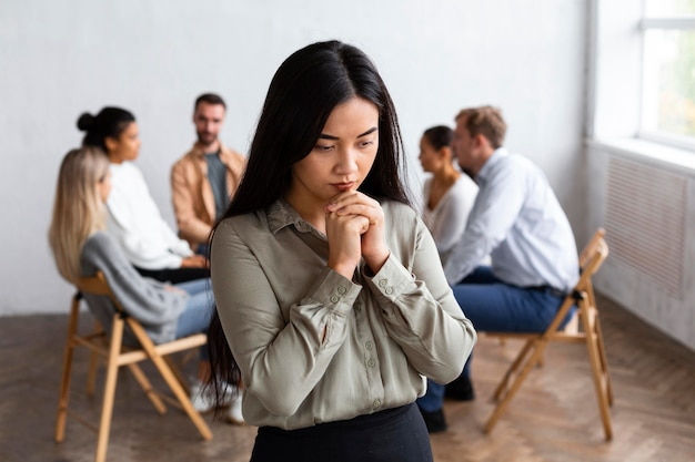 Femme triste lors d'une séance de thérapie de groupe avec des gens assis sur des chaises