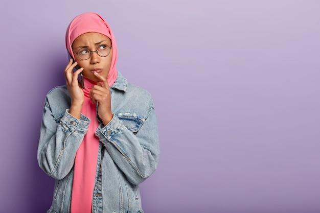 Femme triste à la peau sombre insatisfaite enveloppée dans un hijab rose, porte une veste en jean, des lunettes rondes