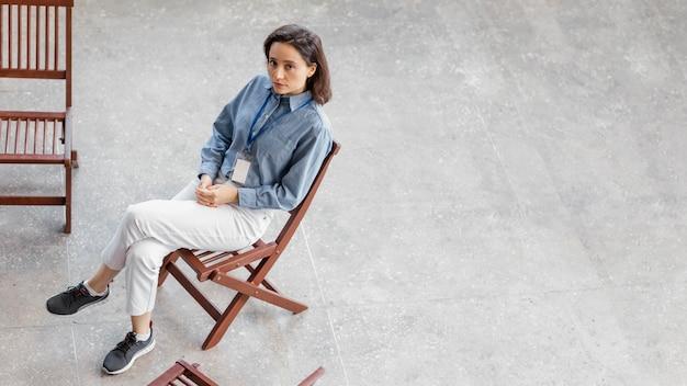 Femme triste plein coup assis sur une chaise