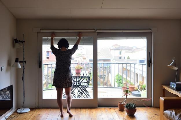 Une femme triste en regardant par la fenêtre à la maison