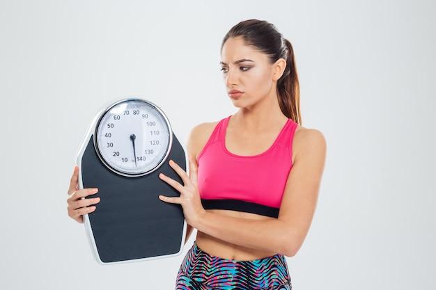 Femme triste de remise en forme tenant une machine de pesage