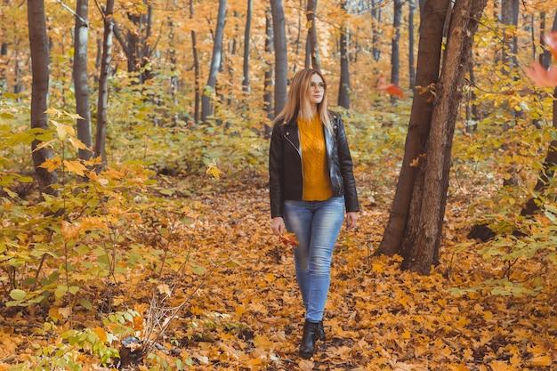 Une femme triste et solitaire donne un coup de pied aux feuilles jaunes en automne. humeur triste et concept de trouble affectif saisonnier.