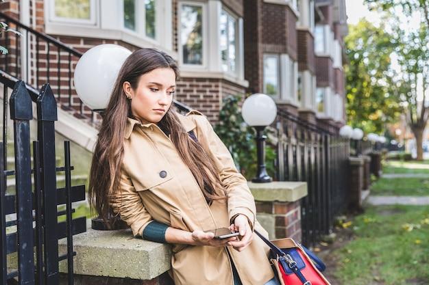 Femme triste avec un téléphone intelligent dans un quartier résidentiel