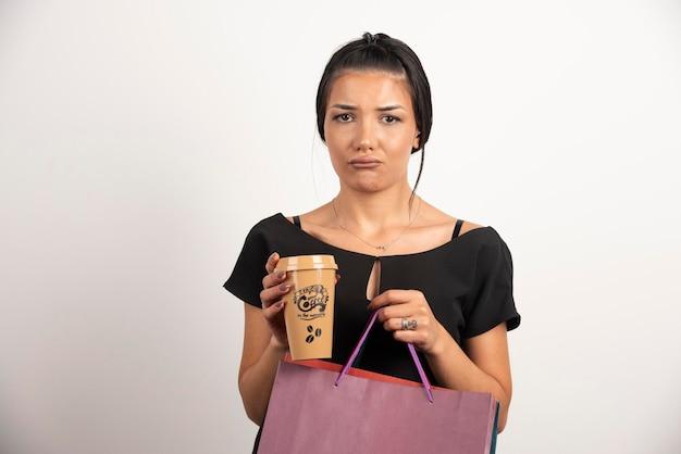Femme triste tenant du café et des sacs à provisions sur un mur blanc.