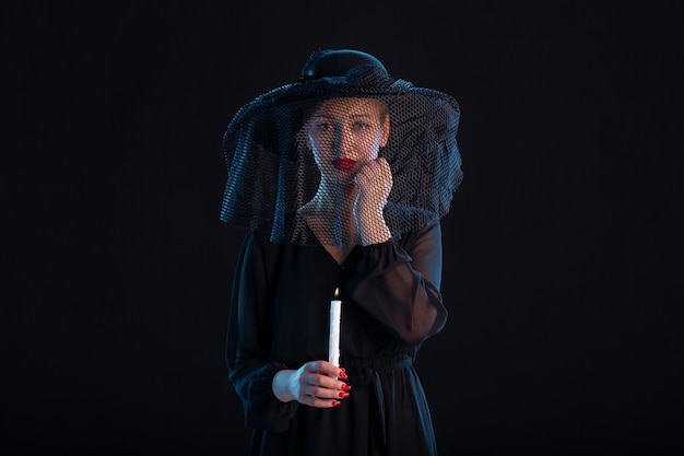 Femme triste vêtue de noir avec une bougie allumée sur la mort funéraire de tristesse noire