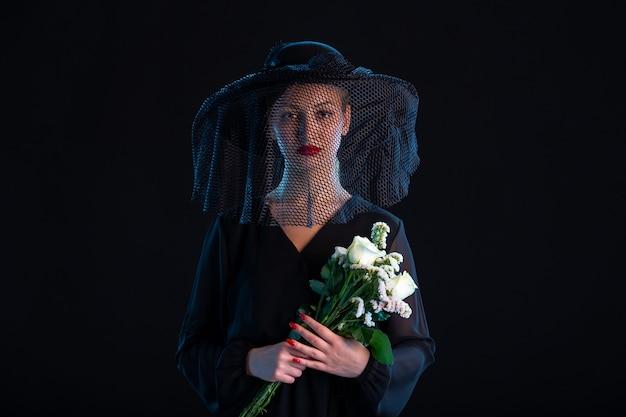 Femme triste vêtue de tout noir avec des fleurs sur la tristesse de la mort funéraire noire