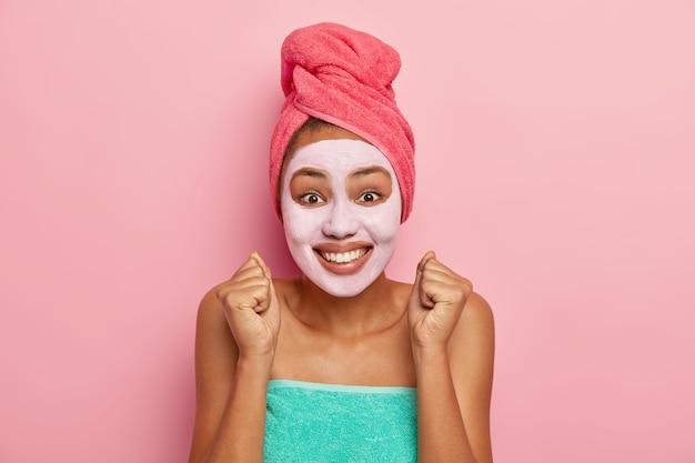 Une femme trop émotive assouplit la peau du visage, lève les poings fermés, regarde positivement la caméra, porte une serviette enveloppée sur la tête et le corps