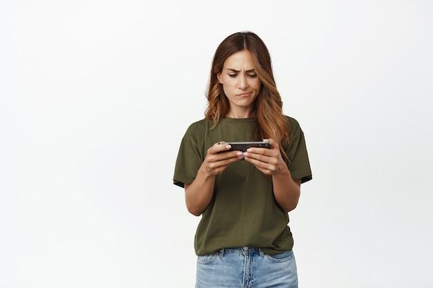 Femme troublée, fronçant les sourcils, regardant bouleversée par l'écran horizontal du smartphone