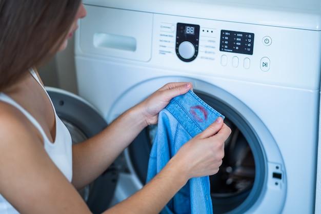 Femme trouvée sur le col de la chemise de son mari, marque de rouge à lèvres rouge pendant le lavage