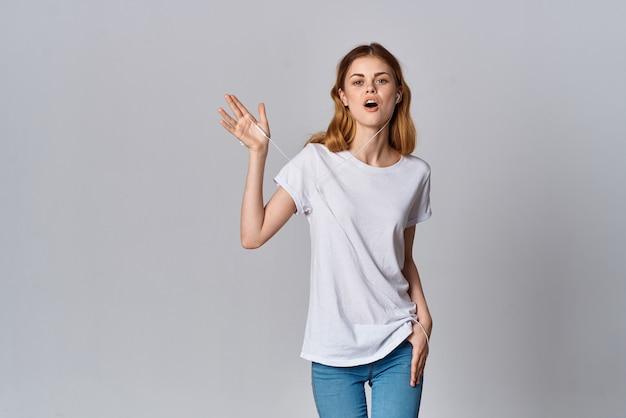 Femme en tshirt blanc mode écoute musique modèle de fond isolé