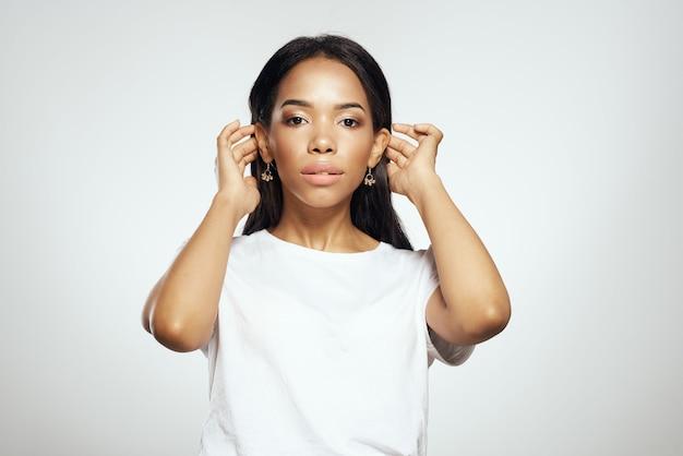 Femme en tshirt blanc noir boucles d'oreilles cheveux longs bijoux fond clair