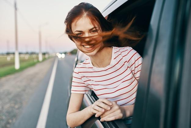 Femme en tshirt rayé modèle de salon de fenêtre de voiture cheveux rouges