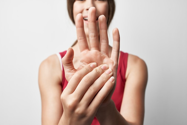 Femme en tshirt rouge traitement de la main des blessures des douleurs articulaires