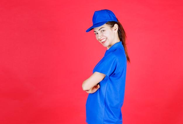 Femme en uniforme bleu donnant des poses positives et neutres.