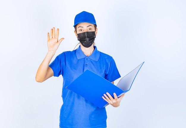 Femme en uniforme bleu et masque noir vérifiant les rapports et faisant attention à une erreur.