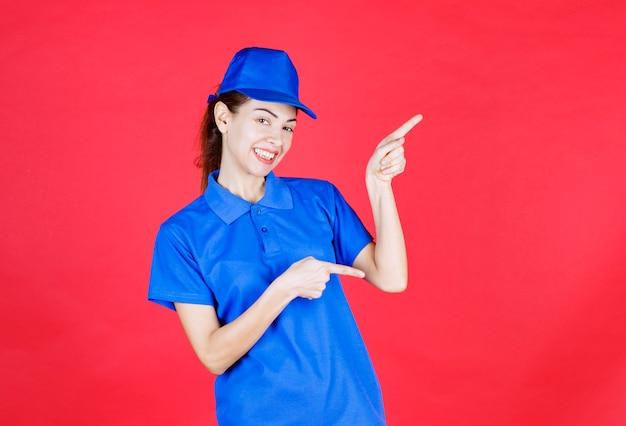 Femme en uniforme bleu montrant quelque chose de côté.