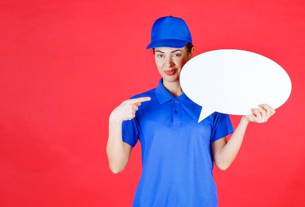Femme en uniforme bleu tenant un tableau d'idées ovale.