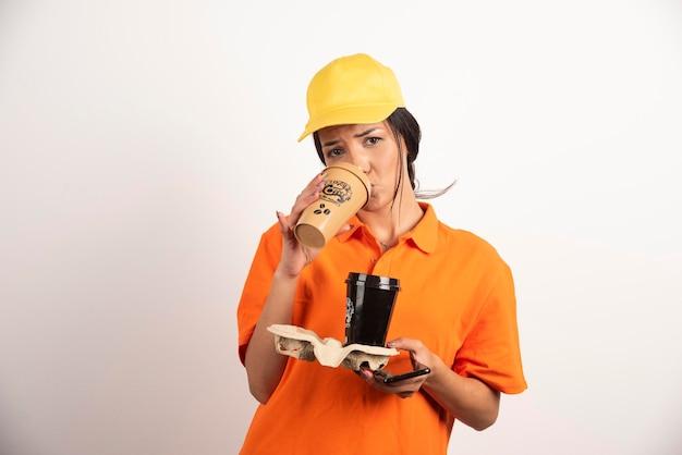 Femme en uniforme buvant dans une tasse de café