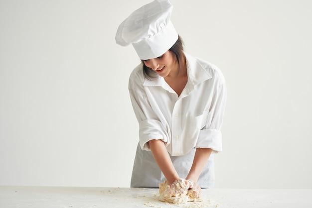 Femme en uniforme de chef boulanger laminage de la pâte cuisine travail