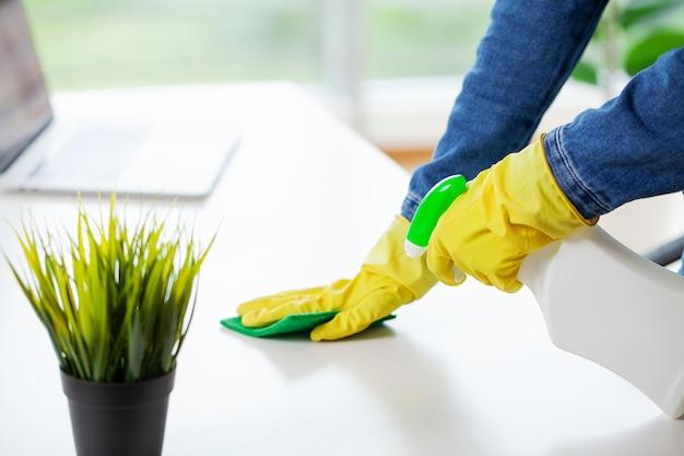 Femme en uniforme avec des fournitures de nettoyage au bureau.