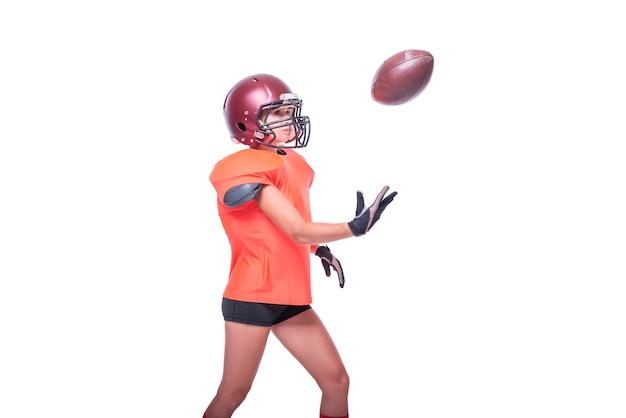Une femme en uniforme de joueur de l'équipe de football américain attrape le ballon. fond blanc. notion de sport. technique mixte