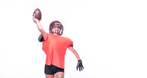 Une femme en uniforme de joueur de l'équipe de football américain lance la balle. notion de sport. technique mixte