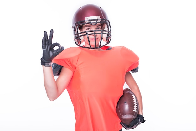 Une femme en uniforme de joueur de l'équipe de football américain montre le signe ok. notion de sport. technique mixte