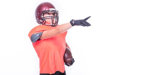 Une femme en uniforme de joueur de l'équipe de football américain pointe du doigt l'espace vide. notion de sport. technique mixte
