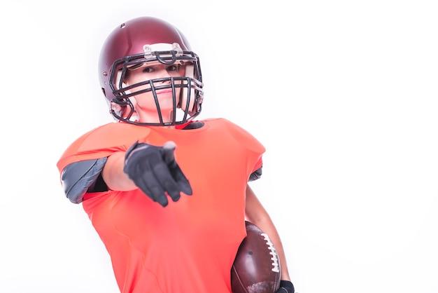 Une femme en uniforme de joueur de l'équipe de football américain pointe son doigt vers la caméra. notion de sport. technique mixte