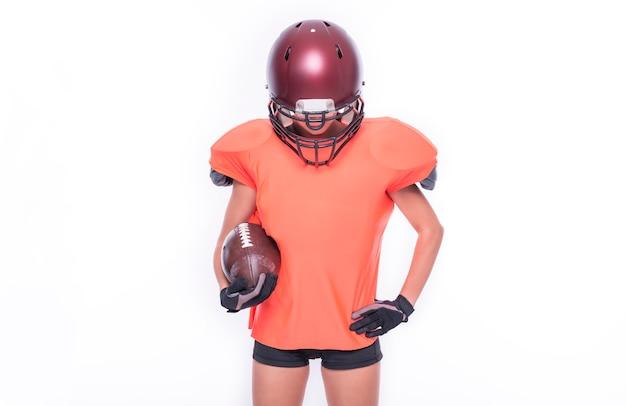 Femme en uniforme d'un joueur de l'équipe de football américain posant avec un ballon sur fond blanc. notion de sport. technique mixte
