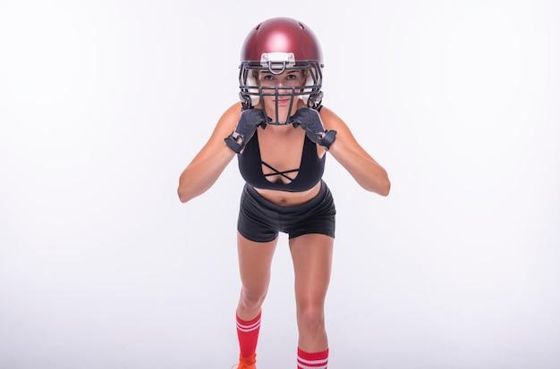 Femme en uniforme d'un joueur de l'équipe de football américain posant sur un fond blanc. notion de sport. technique mixte