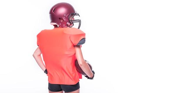 Femme en uniforme d'un joueur de l'équipe de football américain posant en studio. fond blanc. vue arrière. notion de sport. technique mixte
