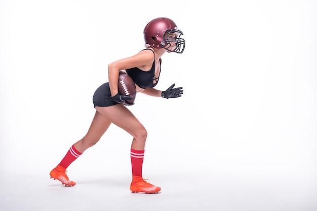 Une femme en uniforme de joueur de l'équipe de football américain se prépare à courir avec le ballon. fond blanc. notion de sport. technique mixte