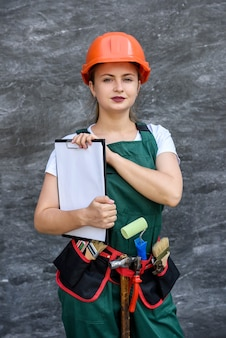 Femme en uniforme de protection et casque posant avec presse-papiers et ceinture à outils